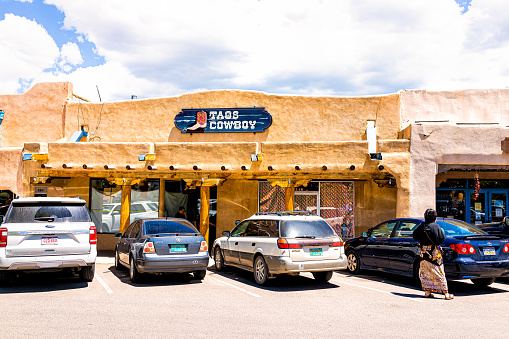 Taos, USA - June 20, 2019: Colorful downtown plaza square in famous town city village with sign exterior for cowboy store shop and cars parked on sunny day
