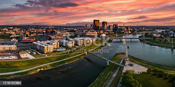 A panoramic aerial drone view over the confluence of the Great Miami and Mad Rivers looking toward downtown Dayton, Ohio under a colorful pink sunset.