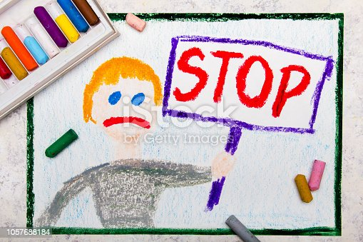 istock Colorful drawing: Sad boy holding a STOP sign in his hand 1057688184