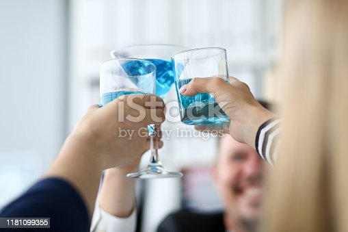 Focus on festive glasses of delicious blue alcohol. People celebrating successful signing profitable contract. Friendly teamwork concept. Blurred background
