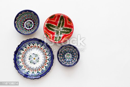 Colorful east ceramic plates and bowls with national pattern in blue and red colors isolated on white background, Tashkent, Uzbekistan. Top view, flat lay