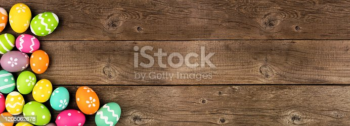 1138213028 istock photo Colorful Easter banner with corner border of Easter Eggs over a dark wood background with copy space 1205062678