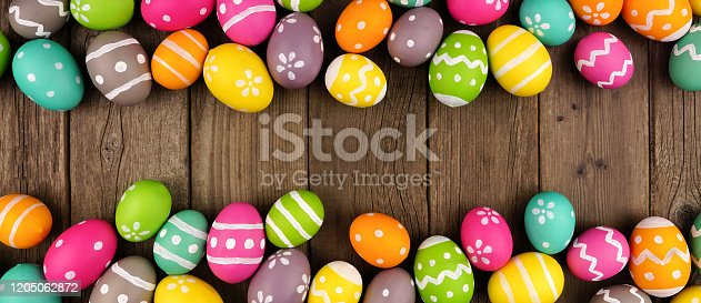 1138213028 istock photo Colorful Easter banner with double border of Easter Eggs over a dark wood background with copy space 1205062872