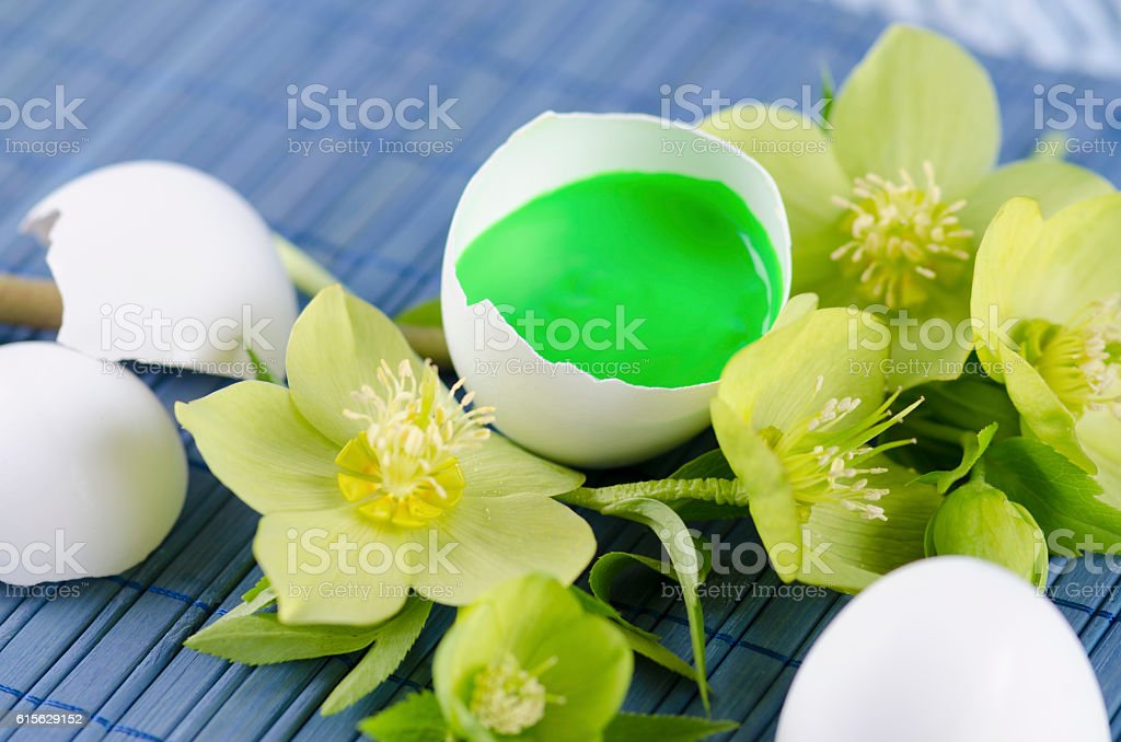 Colorful Easter decoration with egg shell filled with green tempera stock photo