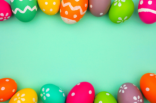 Colorful Easter Egg double border against a turquoise green background. Top view with copy space.