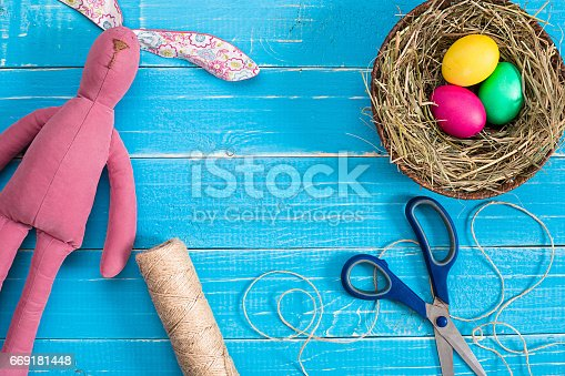 istock Colorful easter egg in nest on blue wood board 669181448