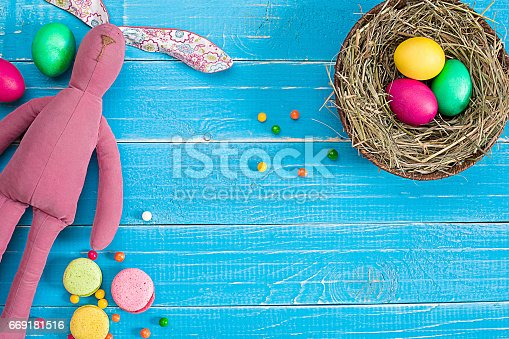 669181586 istock photo Colorful easter egg in nest on blue wood board 669181516