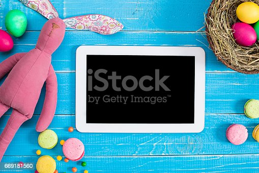 istock Colorful easter egg in nest on blue wood board 669181560