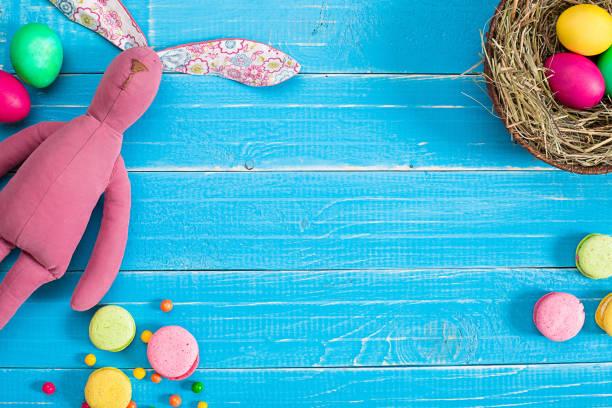 bunte ostereier im nest auf blauen holzplatte - mittagspause schild stock-fotos und bilder