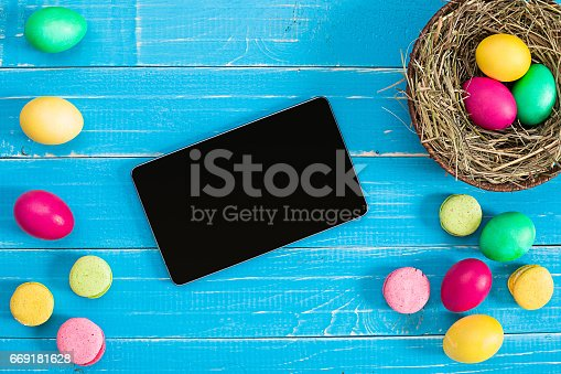 istock Colorful easter egg in nest on blue wood board 669181628