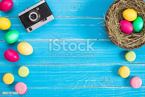 669181586 istock photo Colorful easter egg in nest on blue wood board 669181668