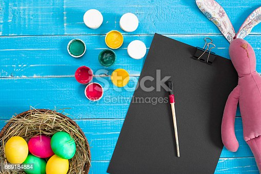 669181586 istock photo Colorful easter egg in nest on blue wood board 669184884