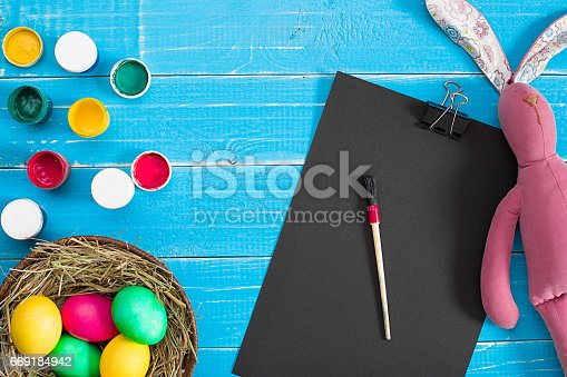 istock Colorful easter egg in nest on blue wood board 669184942