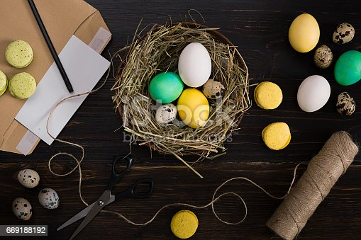 istock Colorful easter egg in nest on dark wood board 669188192