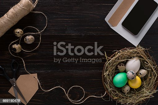 669181586 istock photo Colorful easter egg in nest on dark wood board 669190478