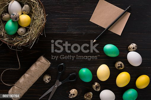 istock Colorful easter egg in nest on dark wood board 669190764