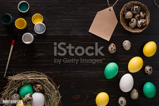 istock Colorful easter egg in nest on dark wood board 669193912