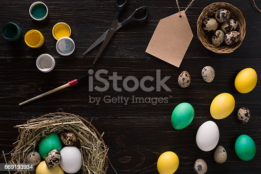 istock Colorful easter egg in nest on dark wood board 669193934