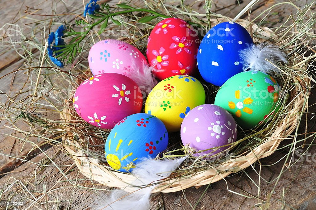 Colorful easter egg nest on wooden background royalty-free stock photo