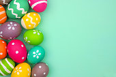Colorful Easter Egg side border against a turquoise green background. Top view with copy space.