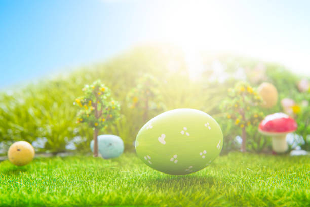 Colorful easter eggs and one big green easter egg on spring green grass stock photo