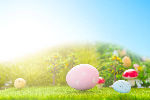 Colorful easter eggs and one big pink easter egg on spring green grass stock photo