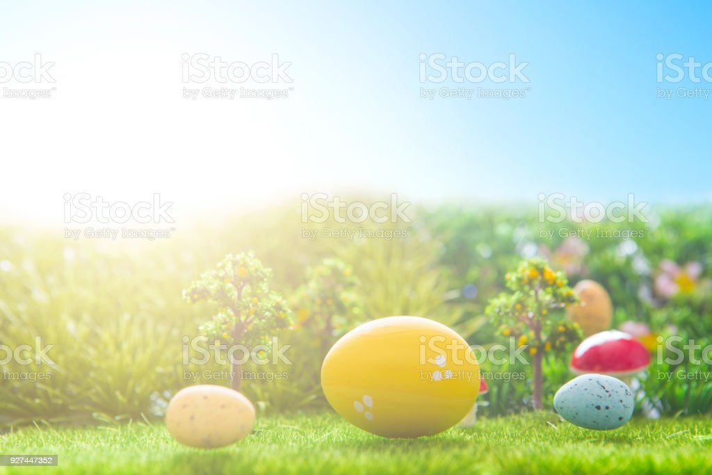 Colorful easter eggs and one big yellow easter egg on spring green grass stock photo