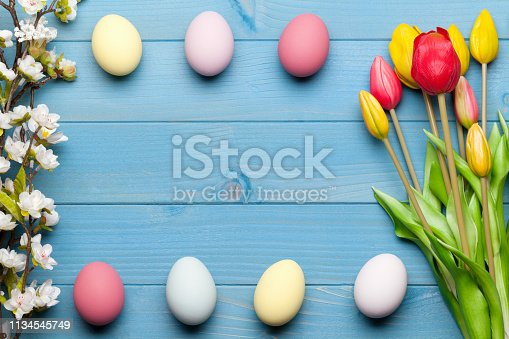 istock Colorful easter eggs and tulips on blue wooden background 1134545749