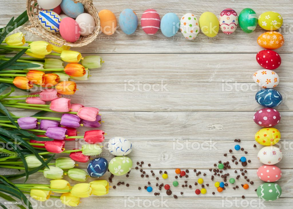 colorful easter eggs and tulips on old wooden stock photo