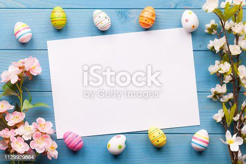 922658520 istock photo Colorful easter eggs background with white blank paper on wooden table 1129929864