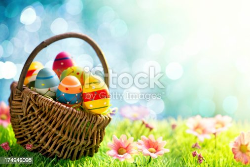 Colorful easter eggs in a basket on meadow
