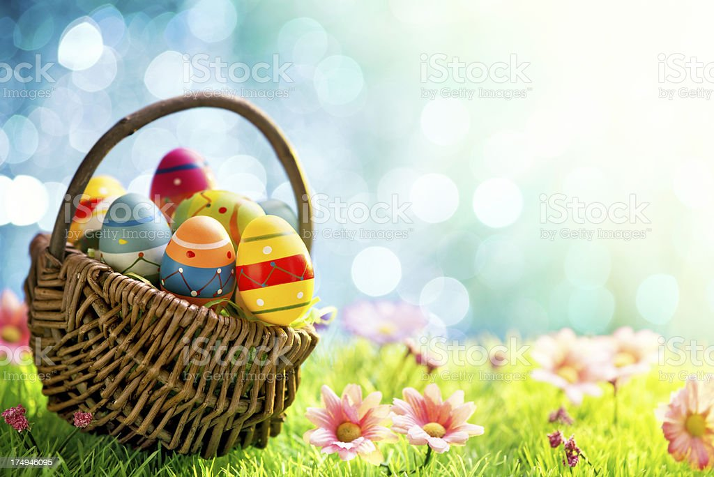 Colorful easter eggs in a basket on meadow stock photo