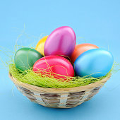 Colorful easter eggs in a basket on softblue background - XXL image