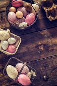 Colorful Easter eggs in a basket on wooden background. They can be painted in various colors and can be given on Easter or springtime. Decorating Easter Eggs is fun and creative activity which you can do with your family. Colored Easter Egg is a universal symbol of Easter.