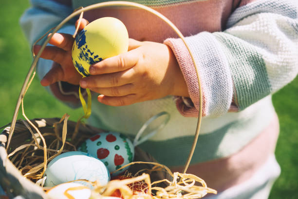 Bunte Ostereier im Korb. Kinder sammeln bemalte Dekoration Eier im Frühlingspark. – Foto