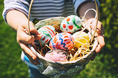 Colorful Easter eggs in basket. Children gathering painted decoration eggs in spring park. Kids hunt for egg outdoors. Festive family traditional play game on Easter.