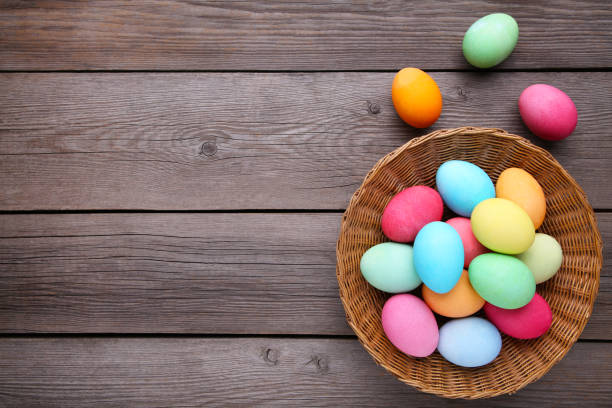 Colorful easter eggs in basket on grey wooden background stock photo