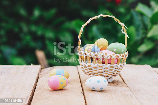 istock Colorful easter eggs in basket on wooden table win copy space. 1072118456