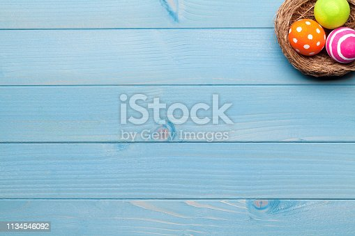 istock Colorful easter eggs in easter nest on blue wooden background 1134546092