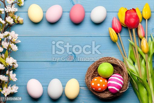 istock Colorful easter eggs in easter nest with flowers on blue wooden background 1134545628