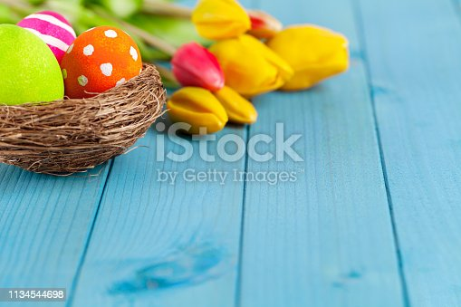 istock Colorful easter eggs in easter nest with tulips on blue wooden background 1134544698