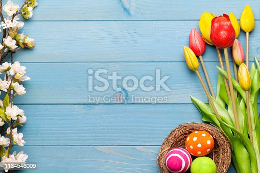 istock Colorful easter eggs in easter nest with tulips on blue wooden background 1134546009