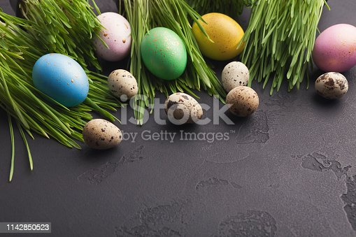 912300146 istock photo Colorful easter eggs in green grass on gray background 1142850523