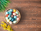 Colorful Easter eggs in nest, feathers and spring flowers on wooden table. Easter holiday decorations , Easter concept background.