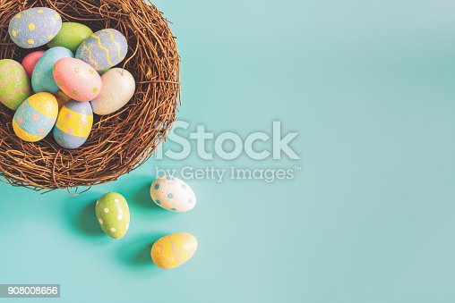 istock Colorful easter eggs in nest on pastel color background with space. 908008656
