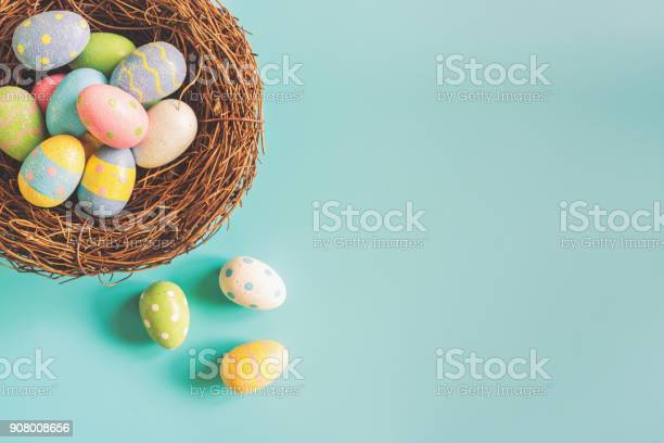 Coloeful easter eggs in nest on pastel color background with space.Colorful easter eggs in nest on pastel color background with space.