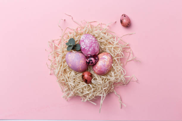 bunte ostereier im nest auf rosa hintergrund. ostertextur - schöne osterbilder stock-fotos und bilder