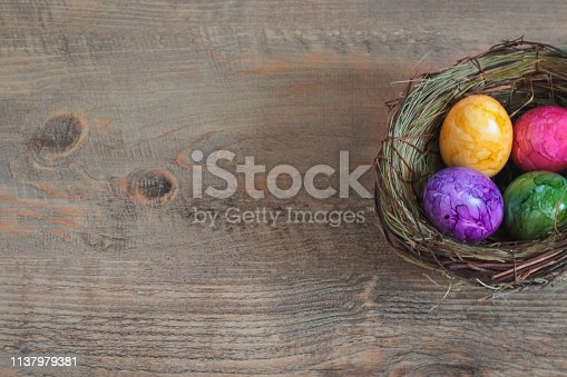 Colorful Boiled Easter Eggs in nest on wood