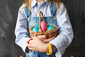 Close-up of unrecognizable girl in rubber bracelets holding wicker basket full of colorful Easter eggs on straw