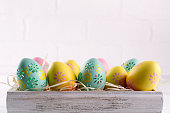 istock Colorful easter eggs in wooden box on white background. Easter holiday background. Copy space 1098417260